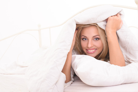 woken: attractive young blonde woman covered with blanket Stock Photo
