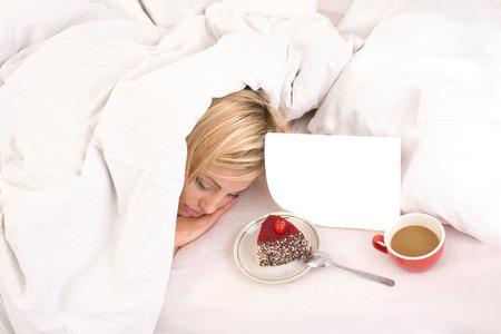 uprzejmości: lekkie śniadanie w łóżku śpiącego młodego blondynka pokryte koc Zdjęcie Seryjne