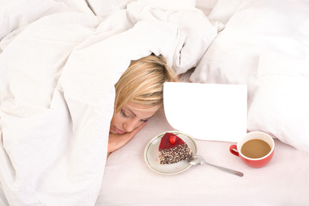 attentions: light breakfast in bed for young sleeping blonde woman covered with blanket