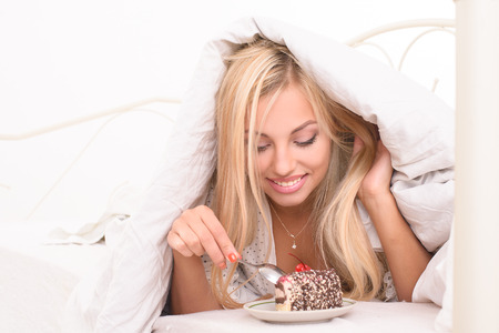 bed linen: young pretty blonde woman lying on bed and eating cake