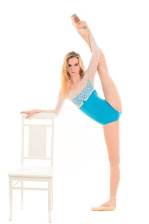flexible: young ballerina with long legs doing stretching exercises at chair isolated on white background Stock Photo