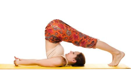 practising: female yogi practising yoga exercises on yellow mat isolated on white background Stock Photo