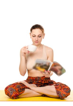 female magazine: sitting female yogi drinking from cup and reading magazine isolated on white background Stock Photo