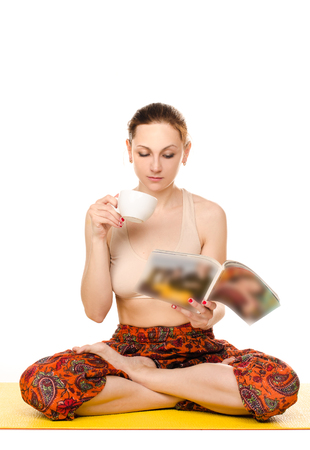 simultaneously: sitting female yogi drinking from cup and reading magazine isolated on white background Stock Photo