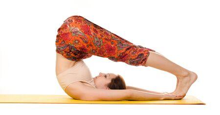 yogi: female yogi practising yoga exercises on yellow mat isolated on white background Stock Photo