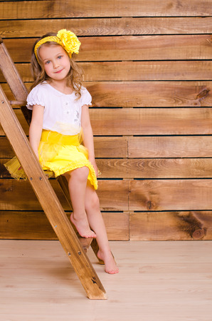 little cute girl with yellow wreath sitting on stairs of ladder on brown wooden wall background