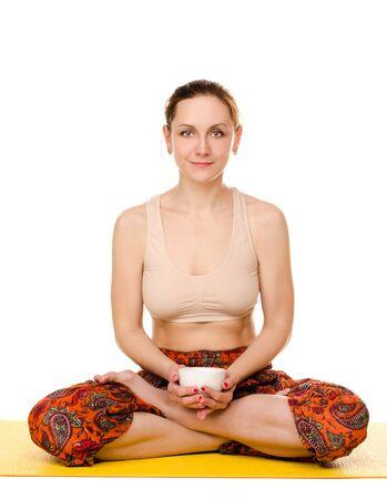 yogi: sitting female yogi with cup isolated on white background Stock Photo