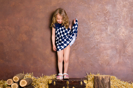 little girl with curly hair standing on old suitcase in retro style in peasant interior Stock Photo