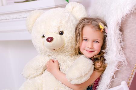 oso de peluche: linda niña abrazando gran oso de peluche blanco en el interior