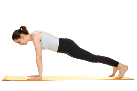 practising: young woman practising yoga exercises on yellow mat isolated on white background Stock Photo