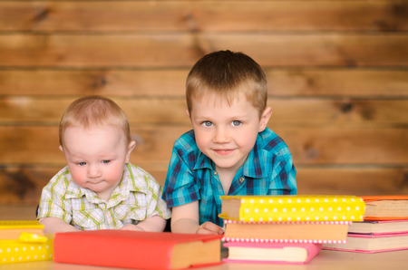 younger: elder and younger little boys with colored books on brown wooden wall background Stock Photo