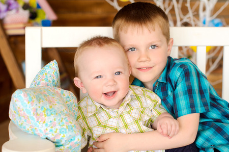 younger: elder and younger brothers kids sitting on bench indoors