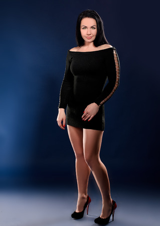 high heels woman: young tempting woman in black gown and high heel shoes on dark blue studio background