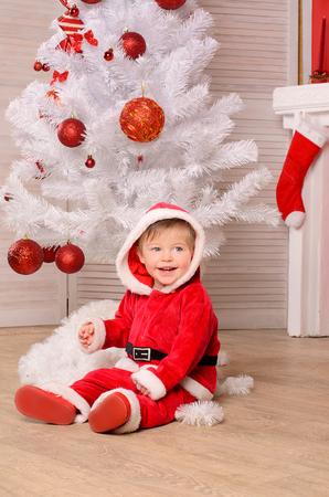 cute smiling little boy in festive attire at christmas tree in red and white indoors Stock Photo