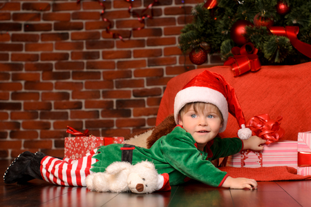 christmas costume: lying little boy in green costume and red hat in christmas interior Stock Photo