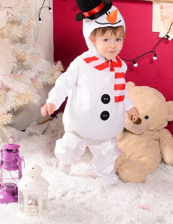 little cute boy in costume of snowman at white christmas tree indoors stock photo 47749105