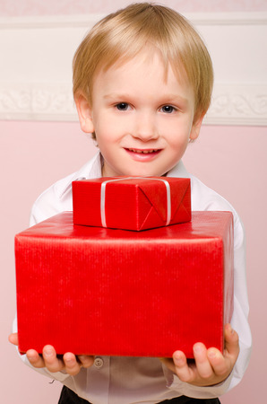 smaller: smiling little boy holding two red boxes of gifts, smaller and bigger, indoors Stock Photo