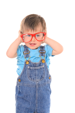 poor eyesight: little funny boy with large red glasses isolated on white background Stock Photo
