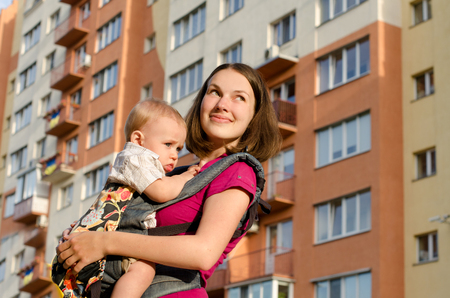 ergonomic: young smiling mommy holding her infant son in ergonomic rucksack on background of multistorey house outdoors Stock Photo