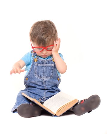 funny glasses: funny little boy with big red glasses reading book isolated on white background