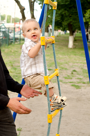rope ladder: toddler boy ascending rope ladder, adult protecting him outdoors Stock Photo