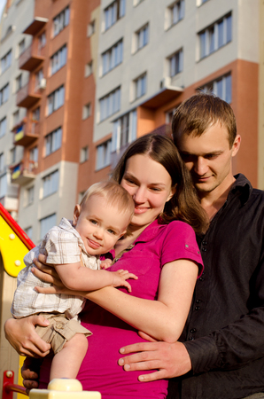 multistory: happy daddy, mommy and little infant son embracing on background of multistory building outdoors Stock Photo