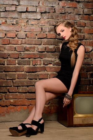 young sensual woman sitting on retro tv set on old brick wall background Stock Photo