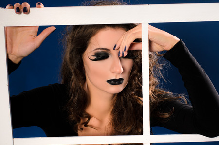 agressive: young woman with professional art agressive black makeup and curly hair holding on white frame on dark blue background Stock Photo