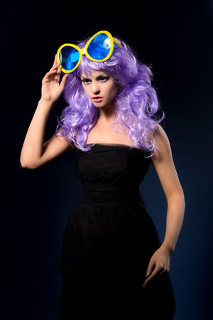 peruke: cosplay girl in black dress and purple wavy wig with big blue sunglasses posing on dark studio background