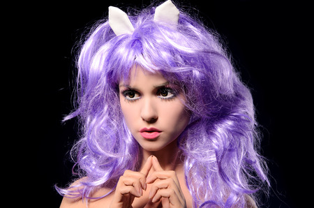 peruke: portrait of attractive cosplay girl with makeup in purple wig with small horns on dark studio background Stock Photo