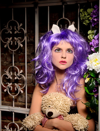 peruke: cosplay girl with makeup in purple wig with soft toy in alcove with flowers Stock Photo