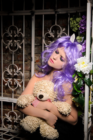anime young: dreaming anime young woman with makeup in purple wig hugging soft toy in pergola