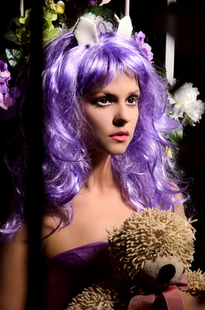 anime young: anime young woman with makeup in purple wig with ears holding soft toy