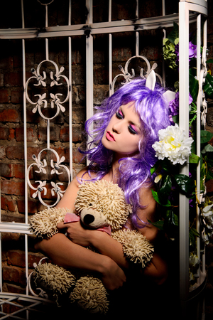 pergola: dreaming anime young woman with makeup in purple wig hugging soft toy in pergola