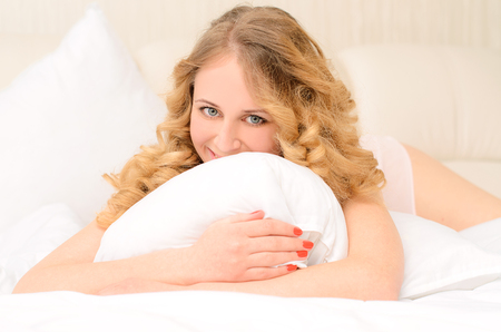 wakening: laughing lying young woman with wavy hair embracing white pillow on bed