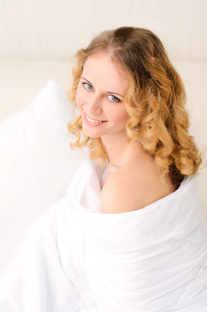 woken: smiling pretty young woman with wavy hair wrapped in white blanket Stock Photo