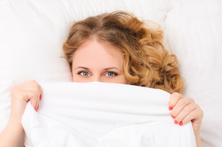 woken: young woman with curly hair hiding under white blanket on bed