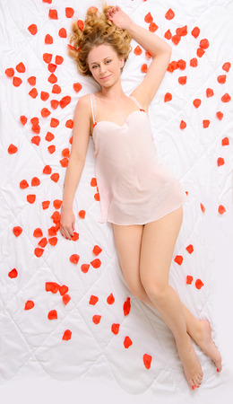 negligee: sexy young woman with wavy hair in negligee lying on white bed with red petals of flowers