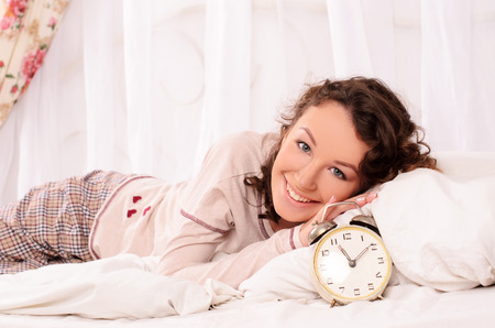 woken: young smiling attractive woman lying on bed with white bedding and alarm clock