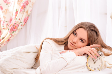 young attractive woman with straight hair in white lying in bed and alarm clock in light bedroom