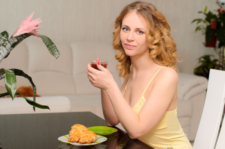 negligee: light breakfast with croissants and cup of tea for young blonde woman with wavy hair in negligee sitting at table indoors Stock Photo
