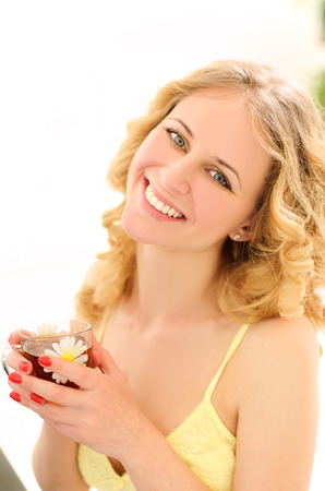 negligee: young attractive laughing blonde woman in negligee with wavy hair holding cup of tea in sunlight