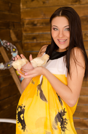 smiling pregnant woman with hand-held chickens