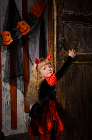 closing: cute halloween devil girl with blonde hair with horns in costume in red and black closing old wooden door indoors