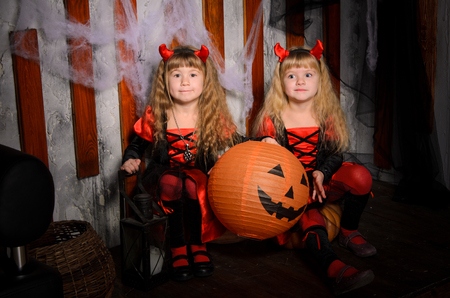 two halloween devils girls, little sisters twins, with horns in costumes in black and red with pumpkins indoors Stock Photo