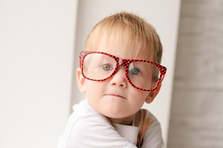 Blond boy in red glasses close up sitting on a background of a white brick wall