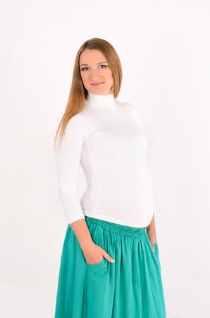 Donna incinta in piedi in una lunga gonna turchese e guardando la foto su uno sfondo completamente bianco