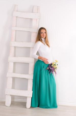 donna incinta con un mazzo di fiori si trova accanto a una scala bianca su uno sfondo completamente bianco