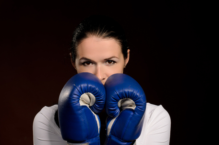 Girl in boxing gloves covers face protection pose against a dark background