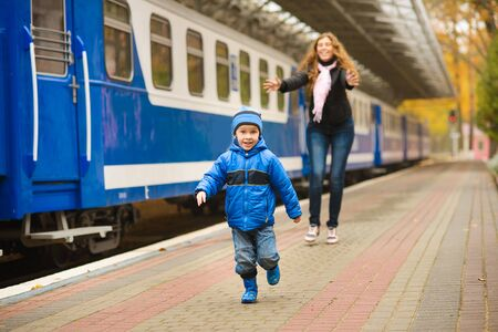 Mom catches up with laughing runaway little son along blue train at station